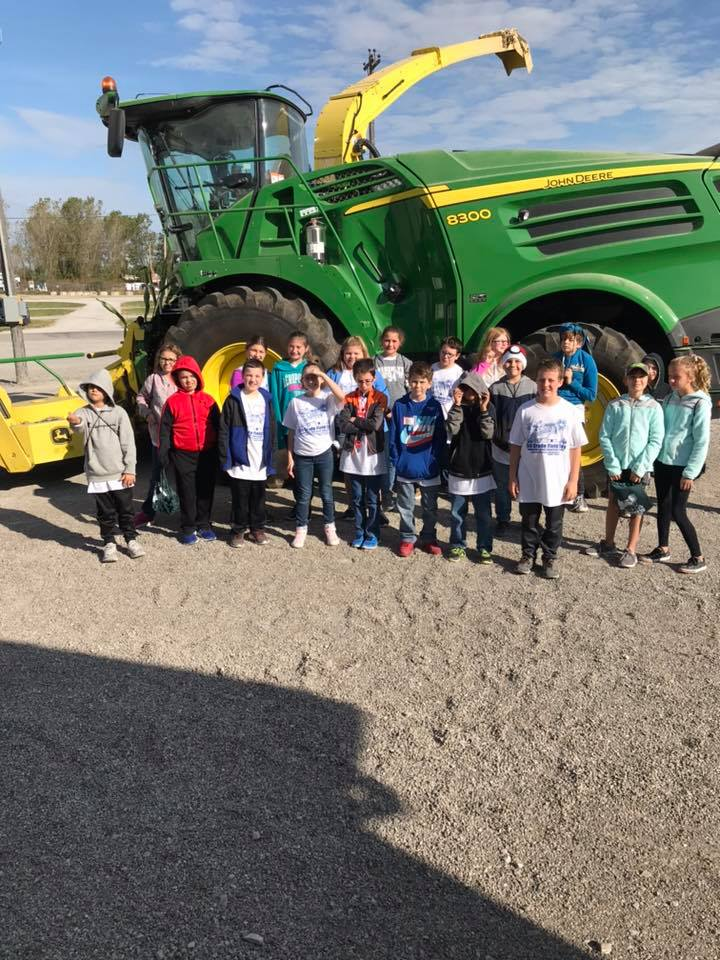 children in front of large tractor